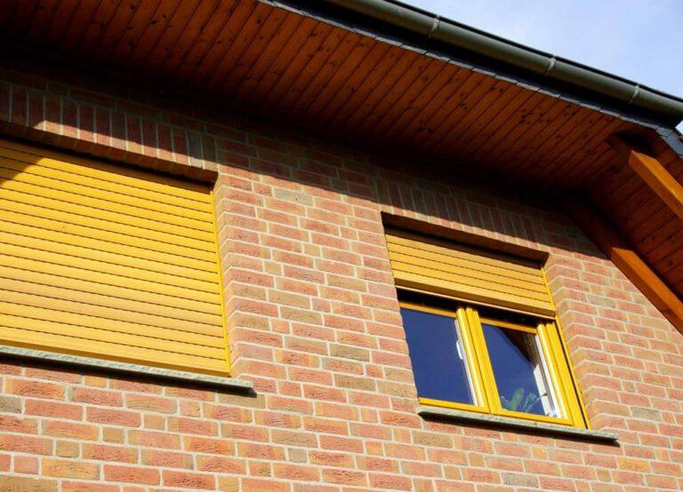 gelbe Rollladen an Fenster in einem Backsteinhaus